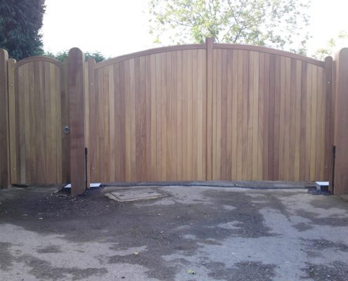 pair of automated curved top iroko tongue and groove gates with single and fencing